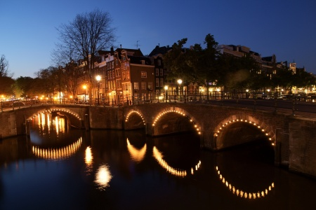 A panorama of a canal at night in Amsterdam.